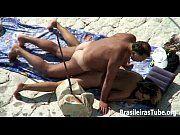 Casal trepando na praia de nudismo