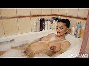 Gravida peituda tomando banho de banheira